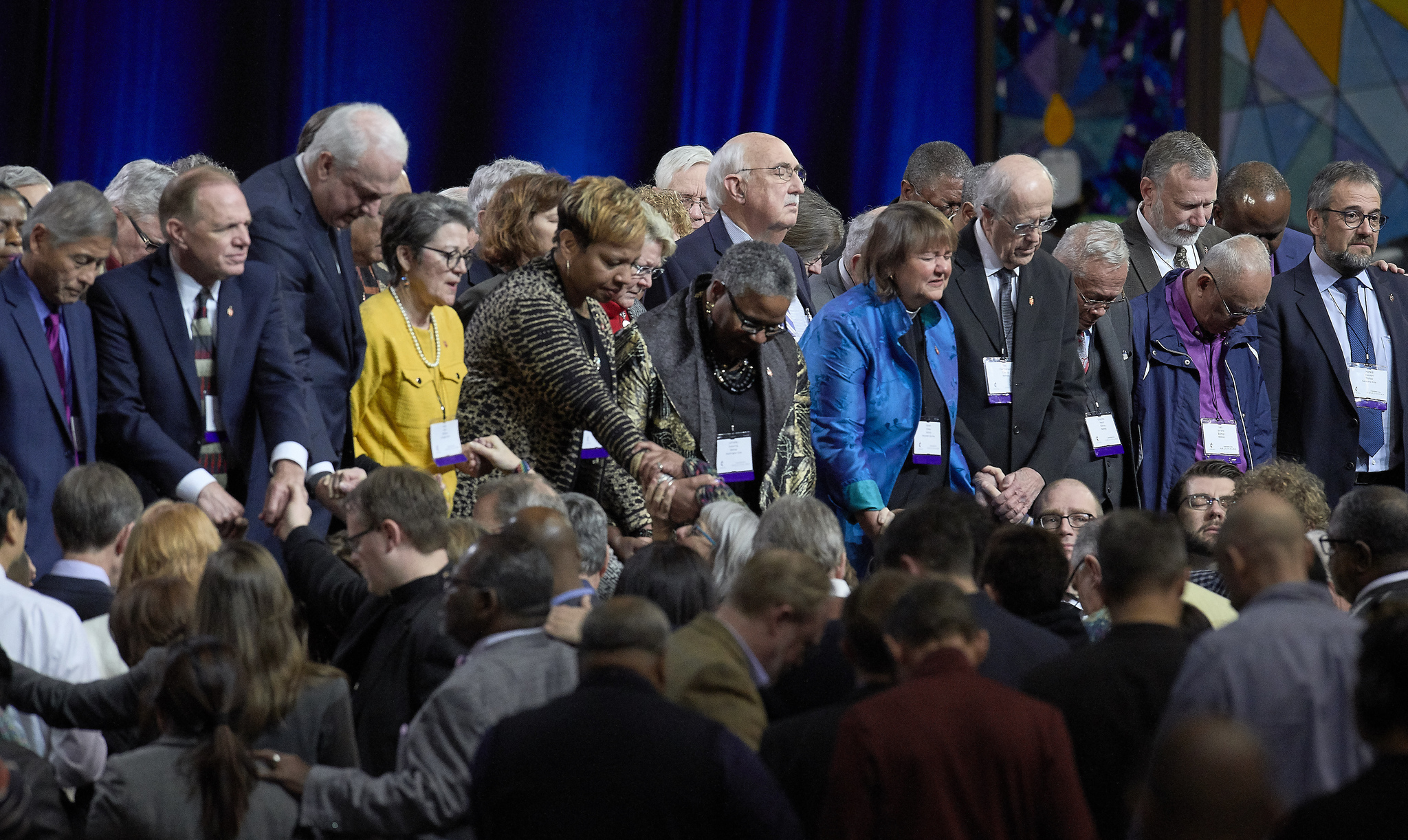 United Methodist bishops and delegates gather together to pray at the front of the stage before a key vote on church policies about homosexuality on February 26, 2019, during the Special Session of the General Conference of The United Methodist Church, held in St. Louis, Missouri. Photo by Paul Jeffrey, UMNS.